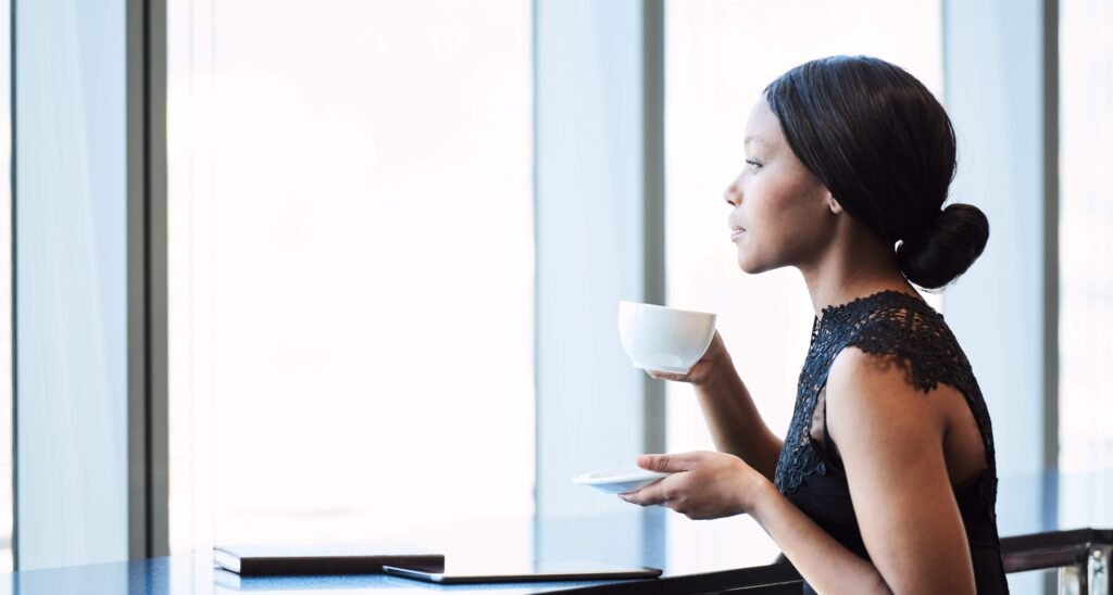 Business woman holding a cup of coffee and looking thoughtfully out a window