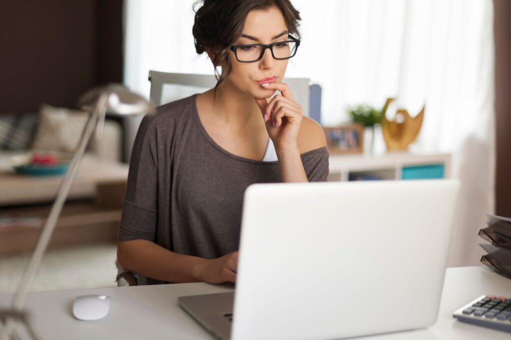 Business woman with glasses working through planning on her laptop