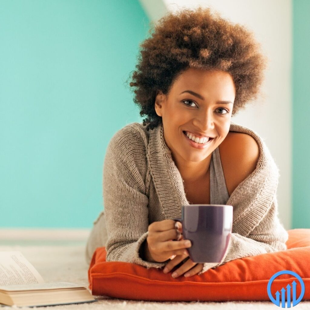 happy, professional African American woman relaxing with a cup of coffee and a book